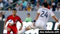 Los Angeles Galaxy midfielder Stefan Ishizaki (24) battles Toronto FC midfielder Sebastian Giovinco, left, for the ball during the first half of an MLS soccer game in Carson, Calif., Saturday, July 4, 2015. The Galaxy won 4-0.