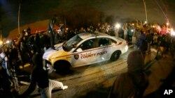 Người biểu tình đập phá và phun chất lỏng bắt lửa lên xe cảnh sát trong khi hình ảnh được truyền hình trực tiếp cho thấy cảnh nhiều người cướp bóc một siêu thị ở Ferguson, Missouri, ngày 24/11/2014.