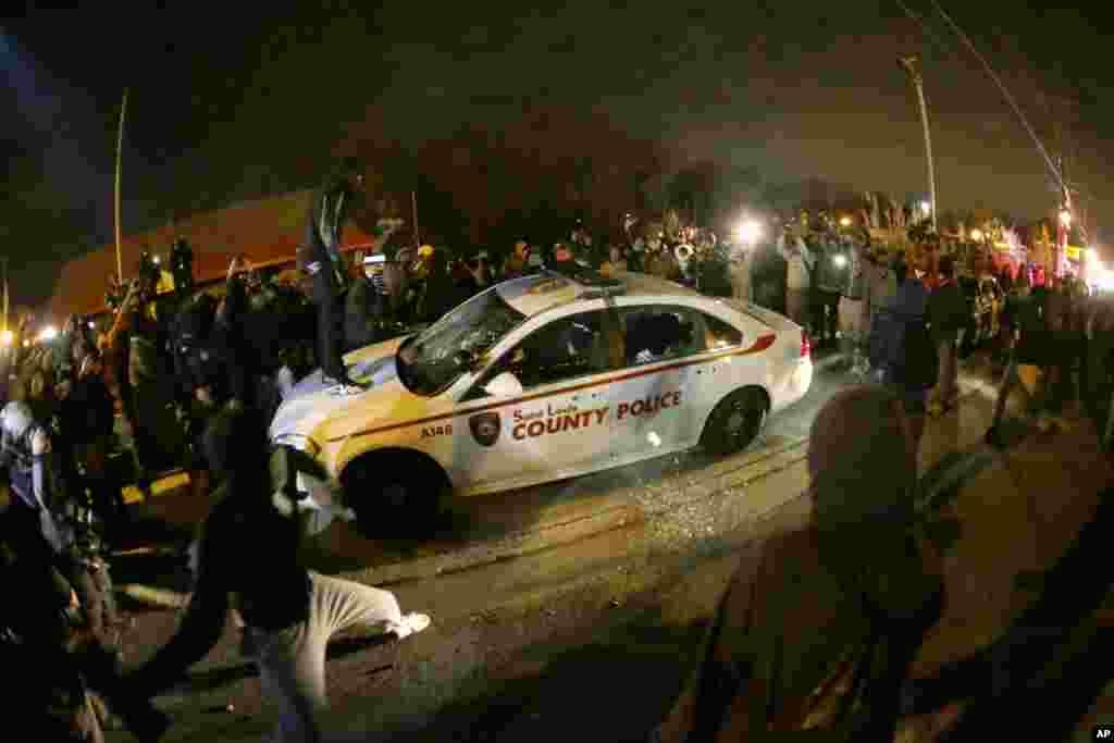 Seorang demonstran menyemprot cairan pembakar ke mobil polisi dekat kantor polisi Ferguson, menyusul keputusan pengadilan untuk tidak mendakwa polisi Darren Wilson dalam penembakan fatal atas Michael Brown, remaja 18 tahun berkulit hitam tak bersenjata, di Ferguson, Missouri (24/11).(AP/Charlie Riedel)
