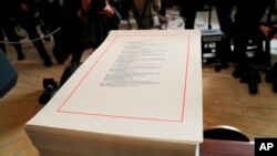 FILE - A copy of a $1.3 trillion spending bill is stacked on a table in the Diplomatic Room of the White House in Washington, March 23, 2018.