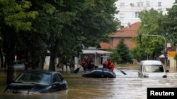 Firefighters evacuate people on a boat in the flooded town of Obrenovac, May 18, 2014.
