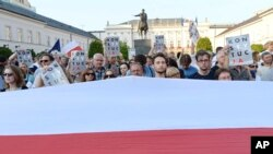 A giant Polish national flag is spread in front of anti-government protesters raising placards reading: Constitution. The protesters are gathered in front of the presidential palace in Warsaw, Poland, July 22, 2017.