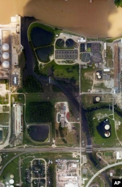 This aerial photo from the National Oceanic and Atmospheric Administration shows floodwaters surrounding the U.S. Oil Recovery Superfund site outside Houston flowing into the San Jacinto River. The Environmental Protection Agency says it has found no evidence toxic waste washed off the site.