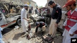 Pakistani police officers examine the site of a bomb blast in a bus stand in Matani near Peshawar, Pakistan, June 5, 2011