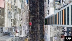 This overhead view shows thousands of protesters marching through the street as they take part in a new rally against a controversial extradition law proposal in Hong Kong on June 16, 2019.