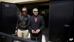 Al-Jazeera English journalists Canadian Mohamed Fahmy, right, and Egyptian Baher Mohammed leave a court after a hearing in their retrial near Tora prison in Cairo, Egypt, March 8, 2015.