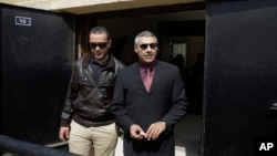 FILE - Al-Jazeera English journalists Canadian Mohamed Fahmy, right, and Egyptian Baher Mohammed leave a court after a hearing in their retrial near Tora prison in Cairo, Egypt, March 8, 2015.