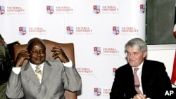 Uganda President Yoweri Museveni, left, with the UK Secretary of State for International Development Andrew Mitchell, right, at the opening of Victoria University in Uganda capital Kampala, September 10, 2011 (file photo).