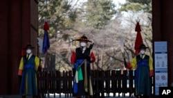 Guardias con uniformes tradicionales y mascarillas ante la entrada del palacio Deoksu en el centro de Seúl, Corea del Sur, el domingo 23 de febrero de 2020. (AP Foto/Lee Jin-man)