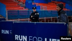 FILE - A NYPD officer stands guard during the ceremonial painting of the New York City Marathon blue line at Central Park in New York.