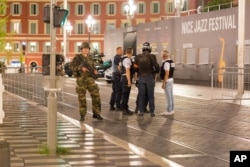 Police officers and a soldier stand by the sealed off area of an attack after a truck drove on to the sidewalk and plowed through a crowd of revelers who'd gathered to watch the fireworks in the resort city of Nice, southern France, July 15, 2016.
