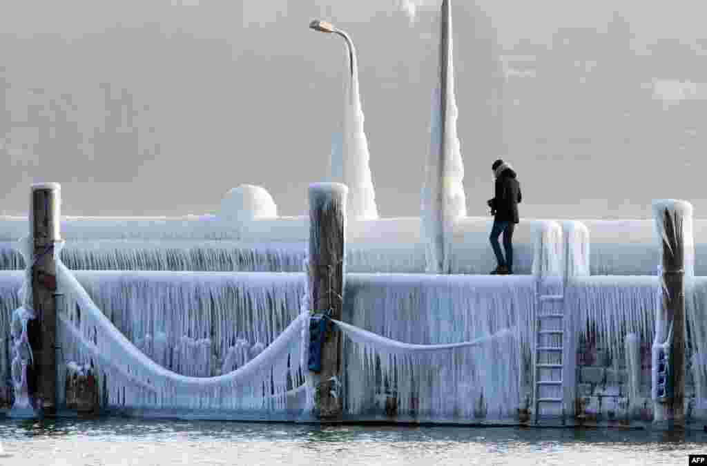 "A man walks along the boardwalk at Lake Constance, which is covered with ice and icicles, in Constance, Germany. A blast of Siberian weather dubbed the ""Beast from the East"" kept the mercury far below zero in huge parts of Europe."