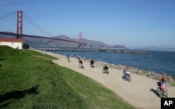 FILE - In this Nov. 25, 2014, photo, bicyclists ride past Crissy Field near the Golden Gate Bridge in San Francisco. Federal authorities have approved a politically conservative group's application to hold a rally at Crissy Field on Aug. 26.