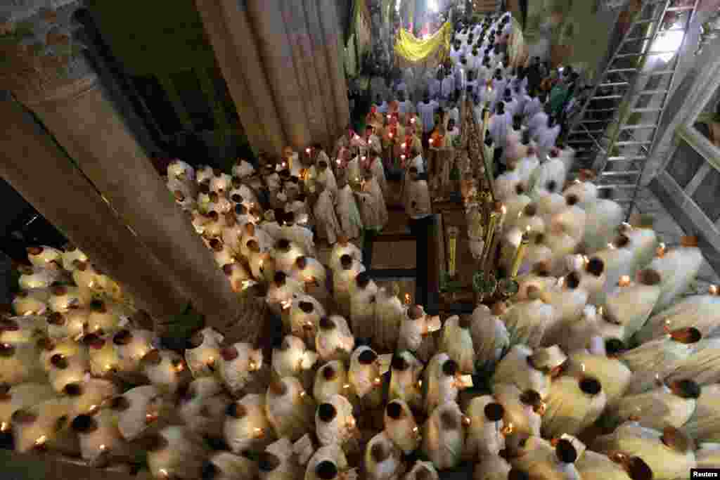 Members of the Catholic clergy hold candles as they take part in a procession at the Washing of the Feet ceremony during Holy Week in the Church of the Holy Sepulchre in Jerusalem's Old City, March 28, 2013.