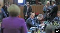 ນາຍົກລັດຖະມົນຕີອັງກິດ ທ່ານ David Cameron (ກາງ) ພວມຫຼຽວເບິ່ງນາຍົກລັດຖະມົນຕີເຢຍຣະມັນ ທ່ານນາງ Angela Merkel (ຊ້າຍ) ທີ່ກອງປະຊຸມສຸດຍອດສະຫະພາບຢູໂຣບ ທີ່ນະຄອນ Brussels (9 ທັນວາ 2011)