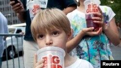 Benjamin, 8, minum soda berukuran besar saat ikut serta dengan ayahnya dalam protes terhadap larangan penjualan soda berukuran besar di New York. (Foto: Dok)