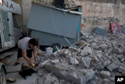 A woman feeds puppies next to rubble, following an earthquake at the port of Kos island, Greece, July 22, 2017.