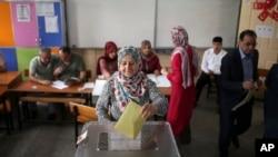 一名土耳其妇女正在把选票放入投票箱