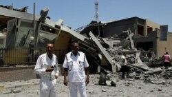 ماموران پلیس لیبی در کنار ساختمانی که می گویند در حمله هوایی ناتو به پایتخت ویران شد. ۱۶ ژوئن ۲۰۱۱