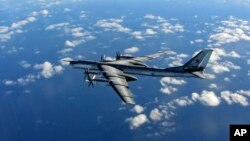 FILE - A Russian long- range bomber, photographed by an intercepting RAF quick reaction Typhoon (QRA) flies in international airspace.