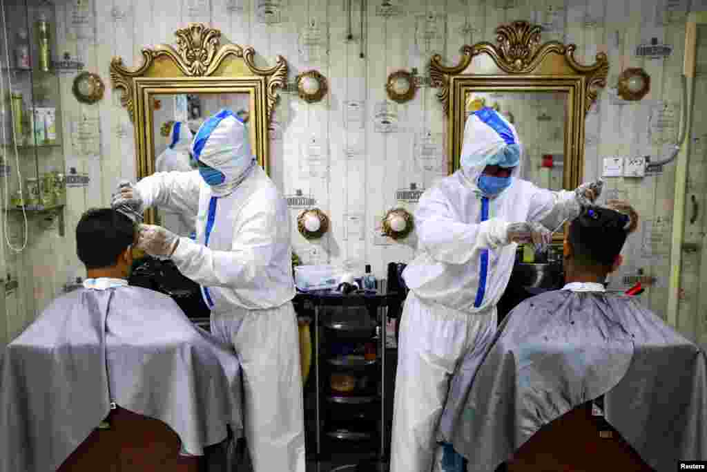 Barbers wearing protective suits and face masks provide hair cut service to the customers inside a salon in Dhaka, Bangladesh.