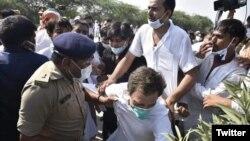 راہول گاندھی زمین پر گرے ہوئے ہیں اور ان کے ساتھی انہیں اٹھانے کی کوشش کر رہے ہیں۔