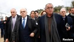 Le ministre grec Yannis Mouzalas escorte le ministre français Bernard Cazeneuve lors de sa visite dans un centre d'enregistrement sur l'île de Lesbos le 4 février 2016.