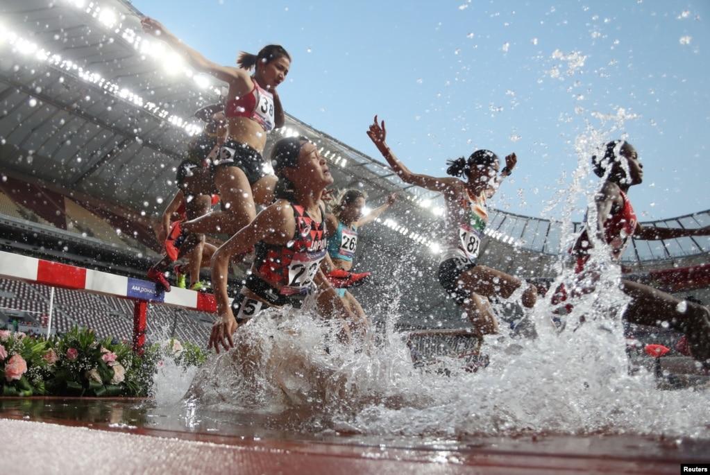 카타르 도하의 칼리아 국제 경기장에서 열린 제23회 아시아육상선수권대회 여자 3000m 장애물 결선에서 선수들이 허들과 물웅덩이를 뛰어넘고 있다.