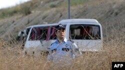 Một sĩ quan cảnh sát Thổ Nhĩ Kỳ đứng trước đống đổ nát của một xe buýt chở binh sĩ bị trúng bom ở Istanbul, Thổ Nhĩ Kỳ, 22 tháng 6, 2010