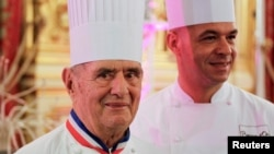 FILE - French chef Paul Bocuse, left, is pictured with his son, Jerome, at the town hall in Lyon, France, Jan. 25, 2011.