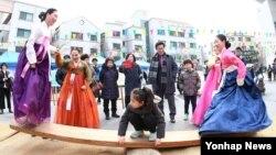 22일 대전 유성구 유성문화원에서 열린 '2016 유성 정월대보름제'에서 한복을 곱게 차려 입은 주민이 널뛰기를 하고 있다.