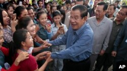 FILE - Cambodia's Prime Minister Hun Sen greets garment workers during a visit to the Phnom Penh Special Economic Zone on the outskirts of Phnom Penh, Cambodia, Aug. 23, 2017.