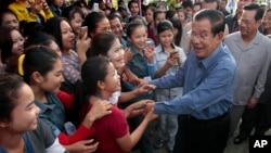 FILE - Cambodia's Prime Minister Hun Sen greets garment workers during a visit to the Phnom Penh Special Economic Zone on the outskirts of Phnom Penh, Cambodia, Aug. 23, 2017. Two Cambodian radio stations said they were being shut down, shrinking the space left for political activity and free expression ahead of next year's general election.