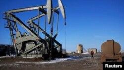 一名工人在北達科他州威利斯頓鎮的石油開採工地前走過。