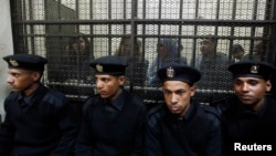 FILE - Some of the 14 Egyptian activists who were accused of working for unlicensed non-governmental organizations (NGOs) and receiving illegal foreign funds, stand in a cage during the opening of their trial in Cairo, Feb. 26, 2012.