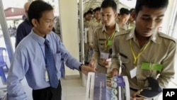 A Cambodian court spokesman Huy Vannak, left, delivers court documents at the court entrance of the U.N.-backed war crimes tribunal in Phnom Penh, Cambodia, Tuesday, Nov. 22, 2011.