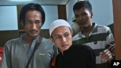 Islamist militant Sigit Indrajit, center, is escorted by plain-clothed police officers after his sentencing proceeding at a district court in Jakarta, Indonesia, Jan. 21, 2014.