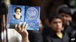 An Iraqi man holds a picture of top Shiite cleric Grand Ayatollah Ali Husseini al-Sistani at a campaign rally for Ammar al-Hakim in Baghdad 5 Mar 2010