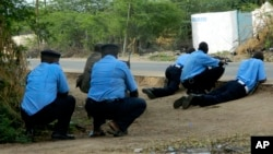 FILE - Kenyan police take cover outside Garissa University College during an attack in Garissa, Kenya, April 2, 2015. Dulyladeyn, the al-Shabab terrorist sought for his role in planning the attack, was killed in an assault this month.