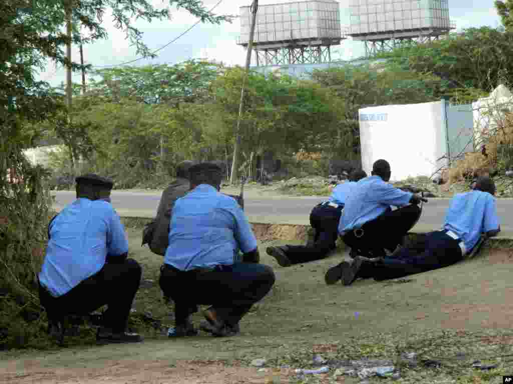 Kenyan police officers take cover outside Garissa University College during an attack by gunmen in Garissa, April 2, 2015.
