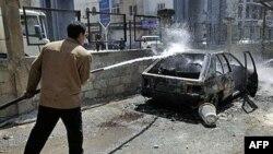 Sirijski radnik poliva vodom automobil koji su zapalili anti vladini demonstranti u Deri, 21. mart 2011.