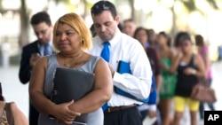 Personas desempleadas hacen mila en la feria de empleos de los Marlins de Miami. El desempleo aumentó al 9,9% en la ciudad.