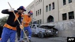Radnici raščišćavaju nakon bombaškog napada u Bagdadu 23. januar, 2011.