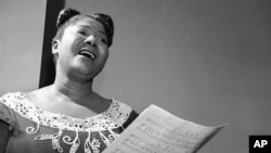 """Mahalia Jackson, the """"Queen of the Gospel Singers,"""" practices a new song in her Chicago apartment, August 30, 1955."""