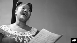 """Mahalia Jackson, """"Queen of the Gospel Singers,"""" practices a new song in her Chicago apartment, Aug. 30, 1955."""