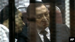 FILE - Ousted Egyptian President Hosni Mubarak, sits in the defendants cage behind protective glass, during a court hearing as he listens to his son Gamal, left, in Cairo, Egypt, May 2014.