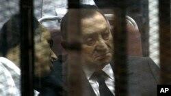 埃及前总统穆巴拉克(右)5月21日在开罗一家法庭坐在笼子里出庭