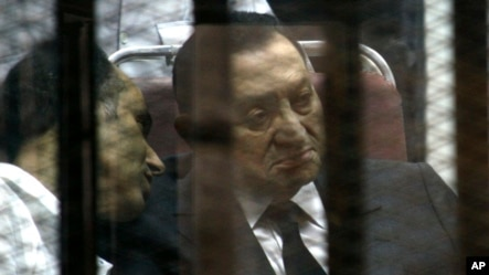 Ousted Egyptian President Hosni Mubarak, sits in the defendants cage behind protective glass, during a court hearing as he listens to his son Gamal, left, in Cairo, Egypt, Wednesday, May 21, 2014.