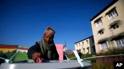 一位尼泊尔选民在巴克塔布的一处投票站投下选票。(2013年11月19日)