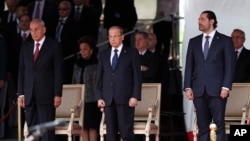 Lebanese President Michel Aoun, center, Lebanese Prime Minister Saad Hariri, right, and Lebanese Parliament Speaker Nabih Berri, left, attend a military parade to mark the 74th anniversary of Lebanon's independence from France in downtown Beirut, Nov. 22, 2017.